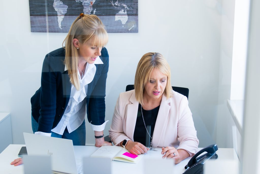 two women in small office talking to desk phone